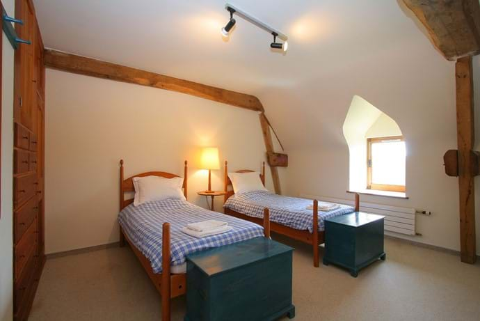 One of the twin bedrooms in The Barn, Boudet, Normandy with plenty of built in storage, a dressing table and view over the orchard and farmland