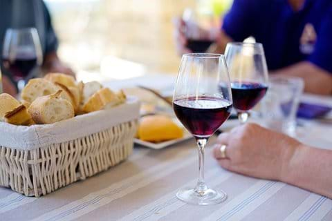 French bread in a basket beside a hand holding a glass of red wine at the table