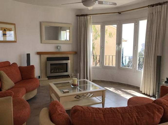 Lounge with double sofas, TV, fireplace and picture windows with sea views