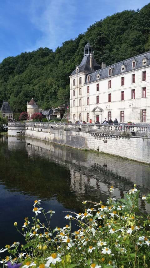 Brantome Abbey beside a very blue river and daisies in the front