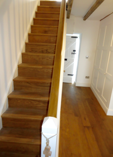 The stairs to the first floor with their sturdy wooden bannister. The front door is in the background