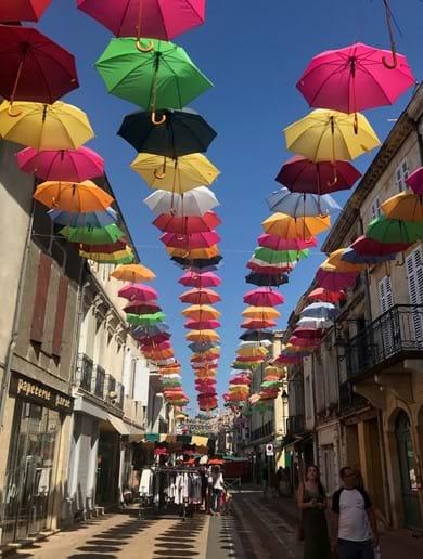 View of colorful umbrellas on street in Sainte=Foy-La-Grande