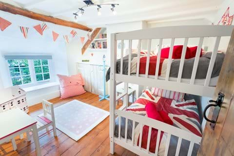 Bunk beds with Unioin Jack duvet covers in a pine-floored Devon cottage bedroom