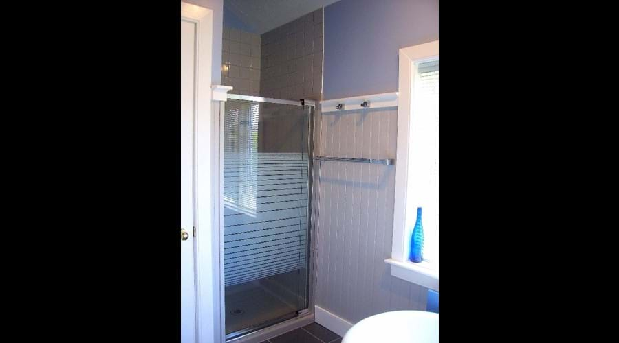 The bathroom also features a glassed-door shower stall.