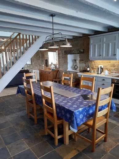 The kitchen is separated from the living area by the oak staircase