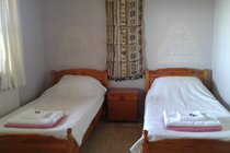 Second bedroom with twin beds and french windows to the terrace