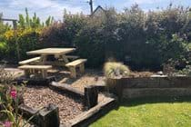 Wooden Picnic table positioned in the enclosed front garden