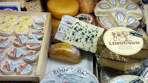 A selection of soft cheese inside a cabinet on a french market stall