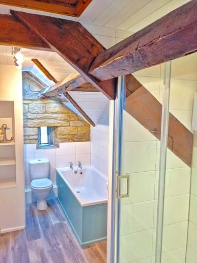 The bathroom has a bath, WC and electric shower. The quirky arrow-slit window offers a sea view too