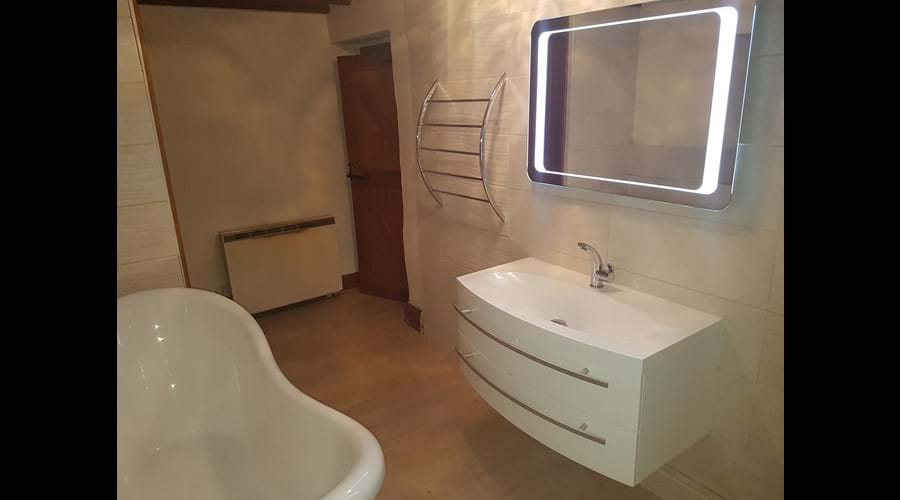 The bathroom has lovely large floating basin and illuminated mirror and complemented with a modern toilet and chrome bathroom accessories.
