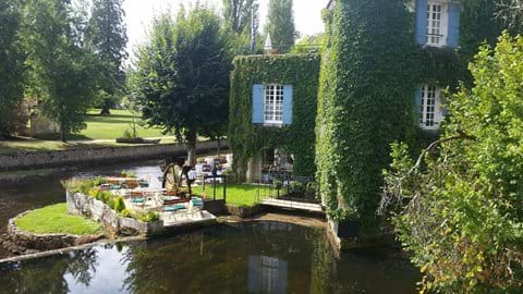 Water mill by small waterfall on river Dronne in Brantome