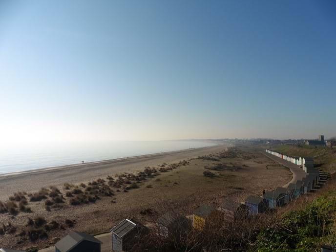 Pakefield beach, beach huts, church and bay beyond