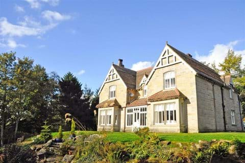 Rothley Lodge, looking up the mature garden towards the imposing stone double fronted house.