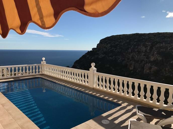 View from the pool terrace with sun awning across to the sea and mountains