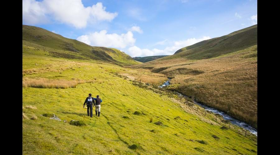 Two people walking in the Cambrian Mountains with a river to their right