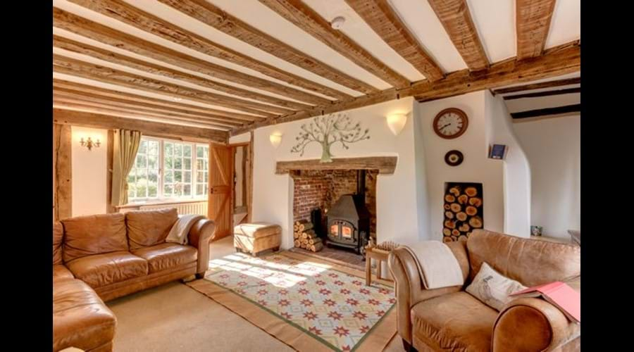 The beamed sitting room, with a log burner in the inglenook fireplace.