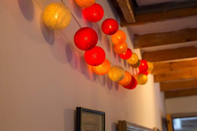 Stings of red and orange lights hanging from the ceiling in a cottage dining room