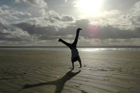A girl turns cartwheels on a beach at sunset