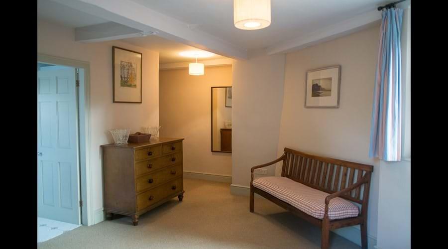 A corner of a ground floor bedroom, door through to en-suite shower-room.