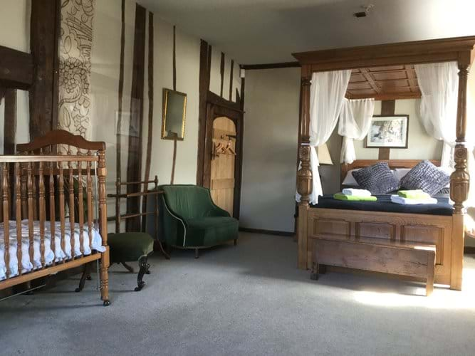 Setting in master bedroom of four poster and cot