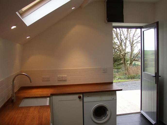 Utility area with washing machine, tumble dryer, additional sink and microwave oven