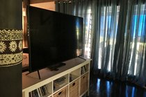 65 inch LED TV with DVD player and remotes.