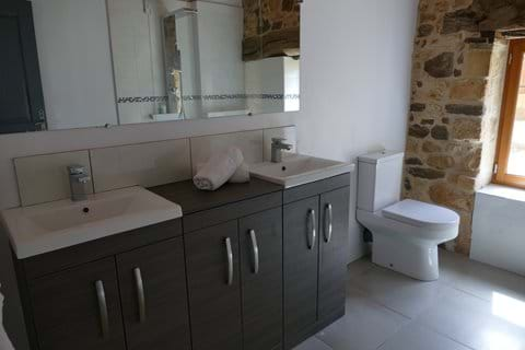 En suite for Bedroom One in Le Noyer with double vanity and walk-in shower