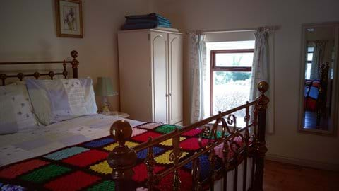 Main bedroom overlooking outbuildings and paths to river and fields.