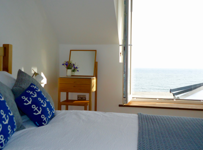 The master bedroom has a king-sized bed, a wall-mounted TV. Both bedrooms enjoy the same stunning sea view