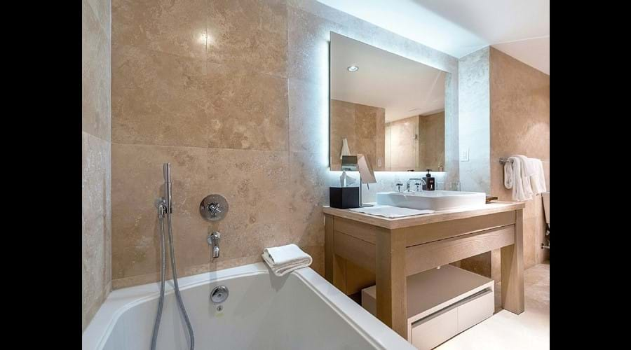 """Bathrooms finished in beautiful, floor-to-ceiling Travertine , Large bath """