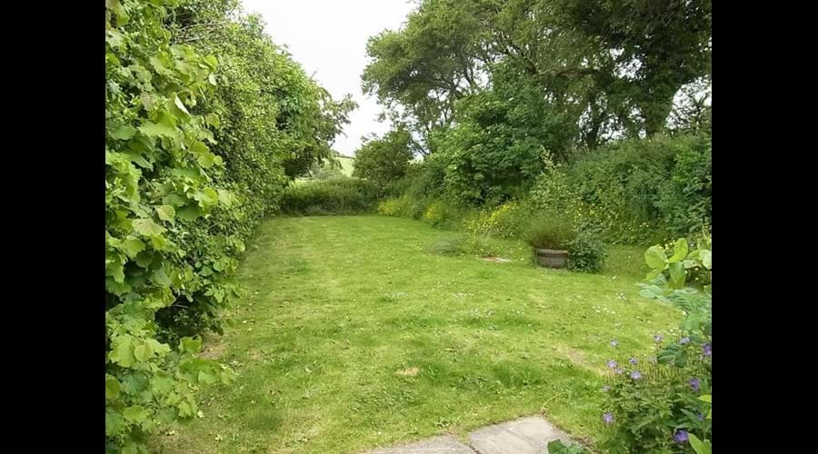 The cottage has two gardens and wooden picnic benches
