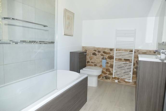 En suite for Bedroom Three has a bath with a shower over