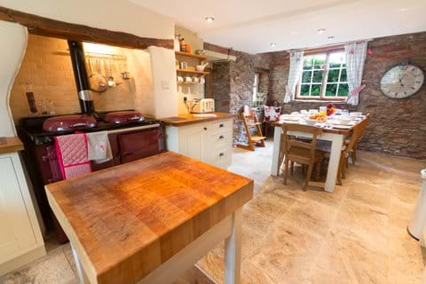 An Exmoor Holiday Cottage kitchen with stove, kitchen block and dining table