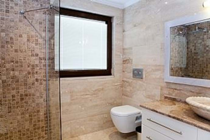 All of the bathrooms are finished in modern travertine/marble
