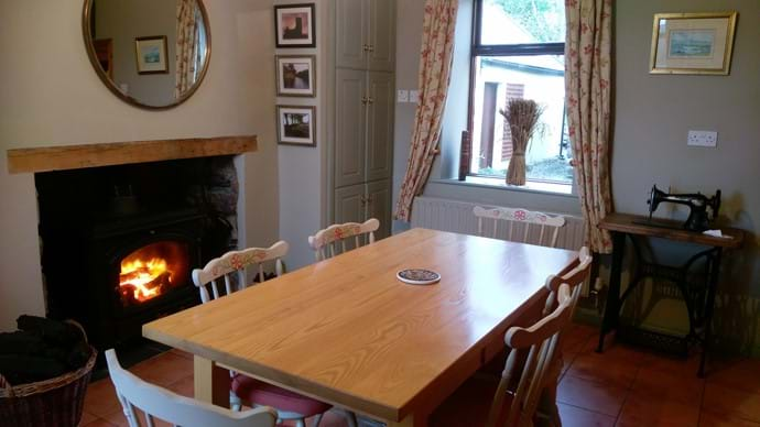 Dining room with the warm glow of a blazing stove while you note the leisurely pace of country life.