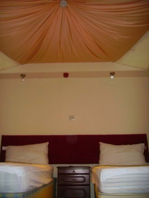 Inside a pod with draped linen ceiling and two single beds
