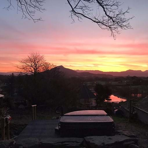photo showing sunrise over the Rhinog mountain range with holiday cottage hot tub in the foreground
