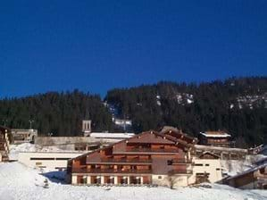 Front of chalet building with village church and Super Chatel chairlift in background