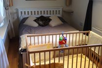 Wooden cot and bedding provided for babies at Bishop