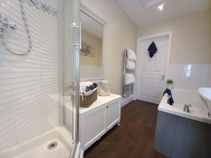 Spacious bathroom and large corner shower and separate bath
