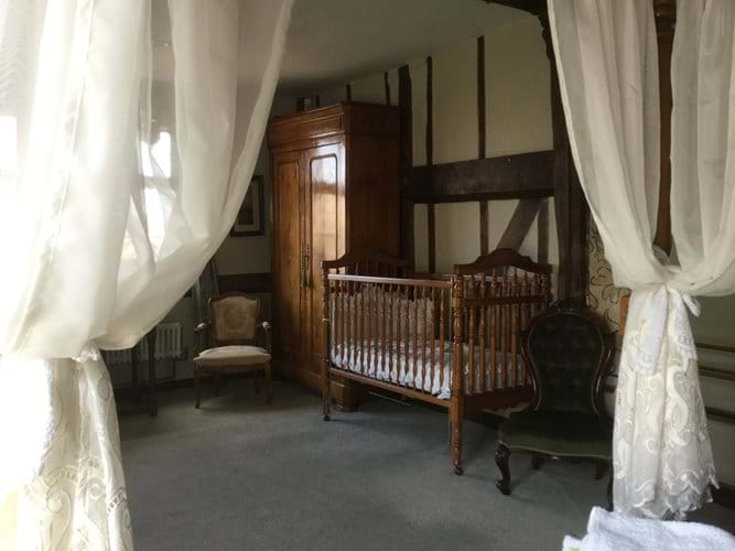 Cot seen from the four poster bed