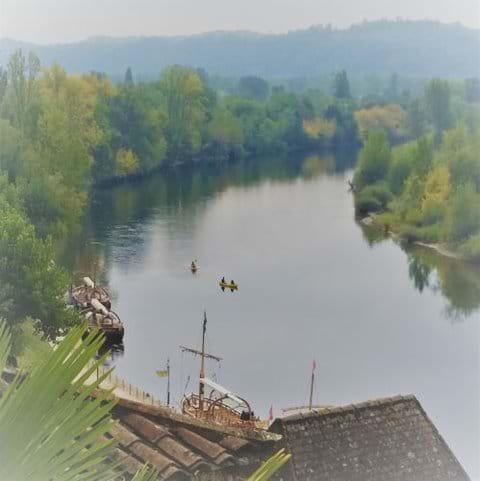 River Dordogne with two green banks and gabarre wooden boat