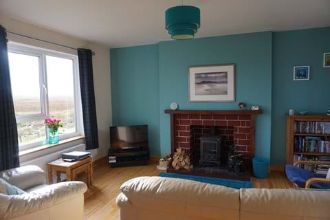 Lounge with views of hills and lochs, woodburner and photo of Luskentyre beach, Harris.