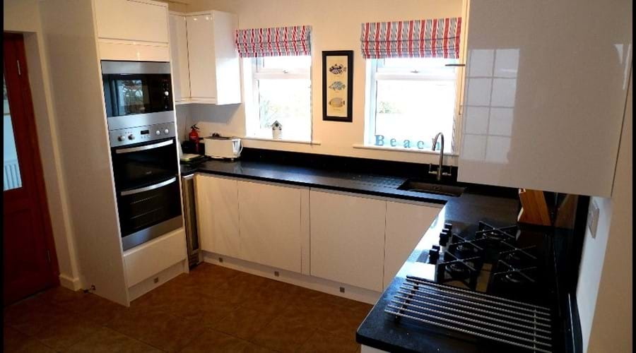 Newly fitted kitchen with fitted double oven, microwave, gas hob, dishwasher and fridge