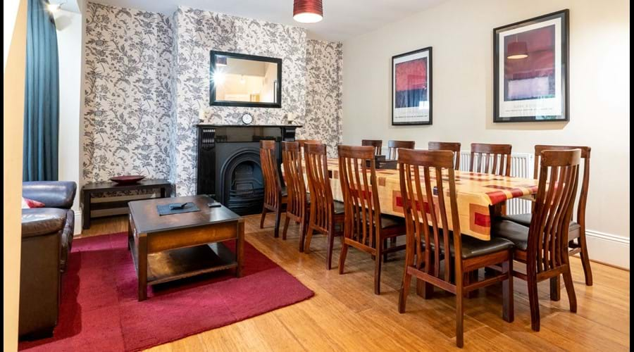 Dining Room with large table and 12 dining chairs, 2 sofas and coffee table.