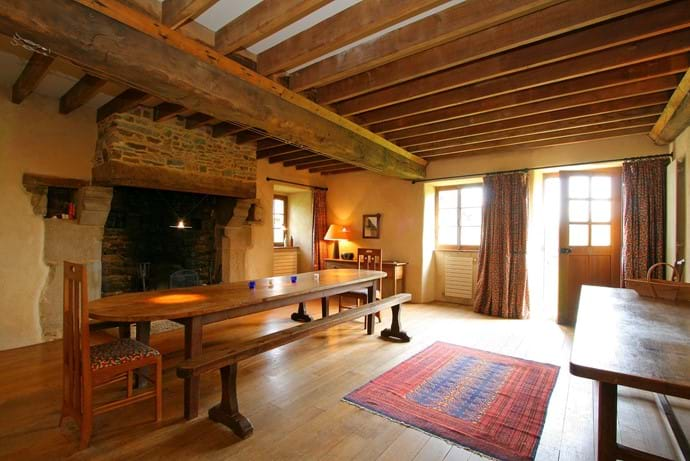 The huge dining room with open fireplace in the Farmhouse