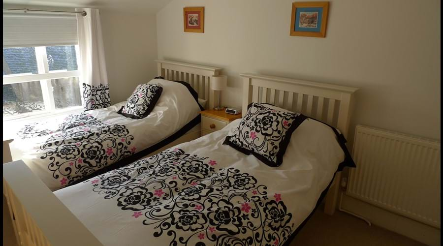 Bedroom 5:  Twin white wood beds with wardrobe, chest of drawers and side table