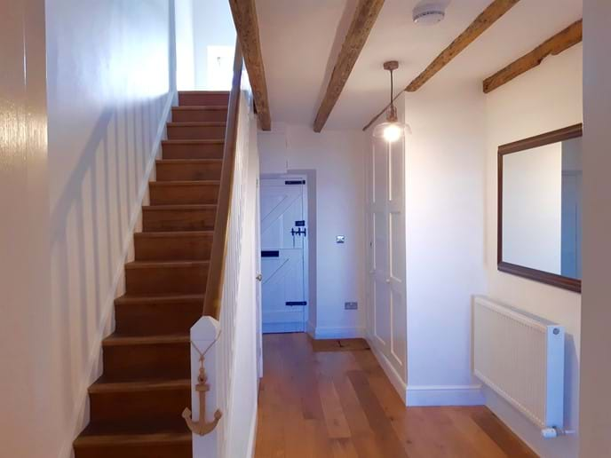 The staircase has a sturdy wooden bannister. The original front door is in the background