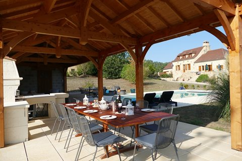 Super large dining table, stone BBQ, fridge and rattan sofas in the pool house