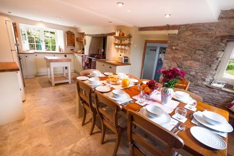 Devon country cottage kitchen with a pine table laid for breakfast